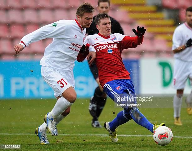 Kristian Kojola of Halle is challenged by Tobias Schweinsteiger of Unterhaching during the third Bundesliga match between SpVgg Unterhaching and...