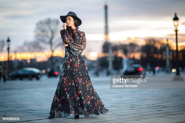 Kristina Castillo fashion and life style blogger wears Celine black boots a Mango black dress with floral print a Mango hat and a Furla bag at Place...