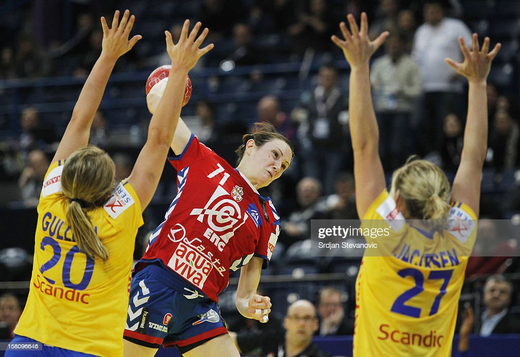 Kristina Liscevic (C) of Serbia jump to shoot the ball over Sabina Jacobsen (R) and Isabelle Gullden (L) of Sweden during the Women's European Handball Championship 2012 Group I main round match between Serbia and Sweden at Arena Hall on December 10, 2012 in Belgrade, Serbia.