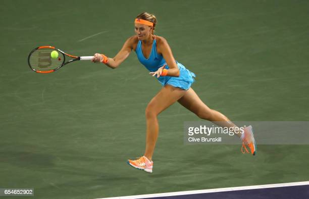 Kristina Mladenovic of France plays a forehand during her straight sets defeat by Elena Vesnina of Russia in their semi final match during day twelve...