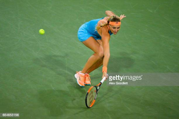 Kristina Mladenovic of France returns a shot to Elena Vesnina of Russia in the women's semifinal on day 12 during the BNP Paribas Open at Indian...