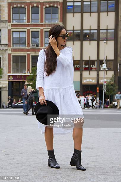 Kristina Petrick wearing white linen Sauths dress with pleats and three quarter length sleeves black fedora hat by Brixton black leather midcalf...