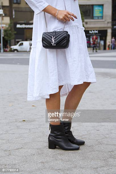 Kristina Petrick wearing white linen Sauths dress with pleats and three quarter length sleeves black leather midcalf booties by Seychelles with...
