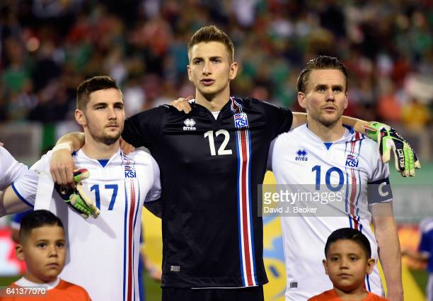 Kristinn Freyr Sigurdsson goalkeeper Frederik Schram and David Thor Vidarsson of Iceland stand on the field during Iceland's national anthem before...