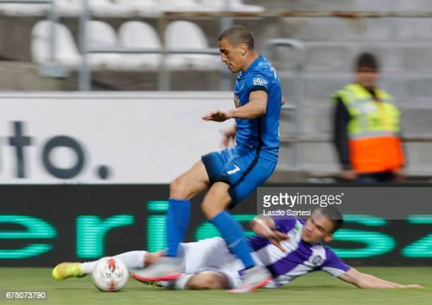 Kristof Szucs of Ujpest FC slide tackles Myke Bouard Ramos of MTK Budapest during the Hungarian OTP Bank Liga match between Ujpest FC and MTK...