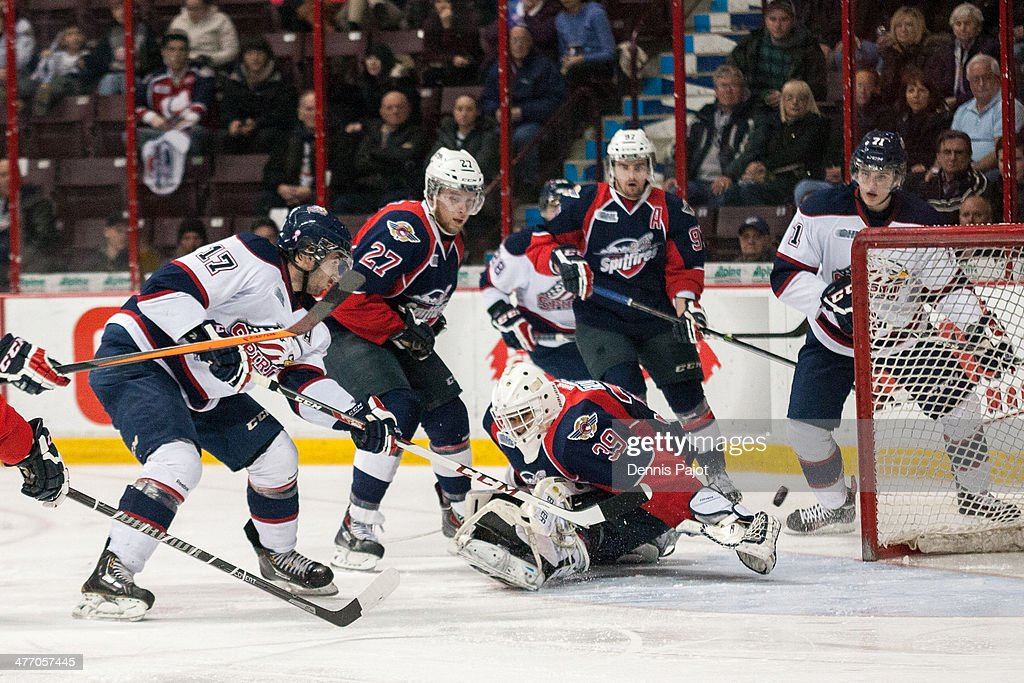 Kristoff Kontos #17 of the Saginaw Spirit fires a shot against past Alex Fotinos #39 of the Windsor Spitfires on March 6, 2014 at the WFCU Centre in Windsor, Ontario, Canada.