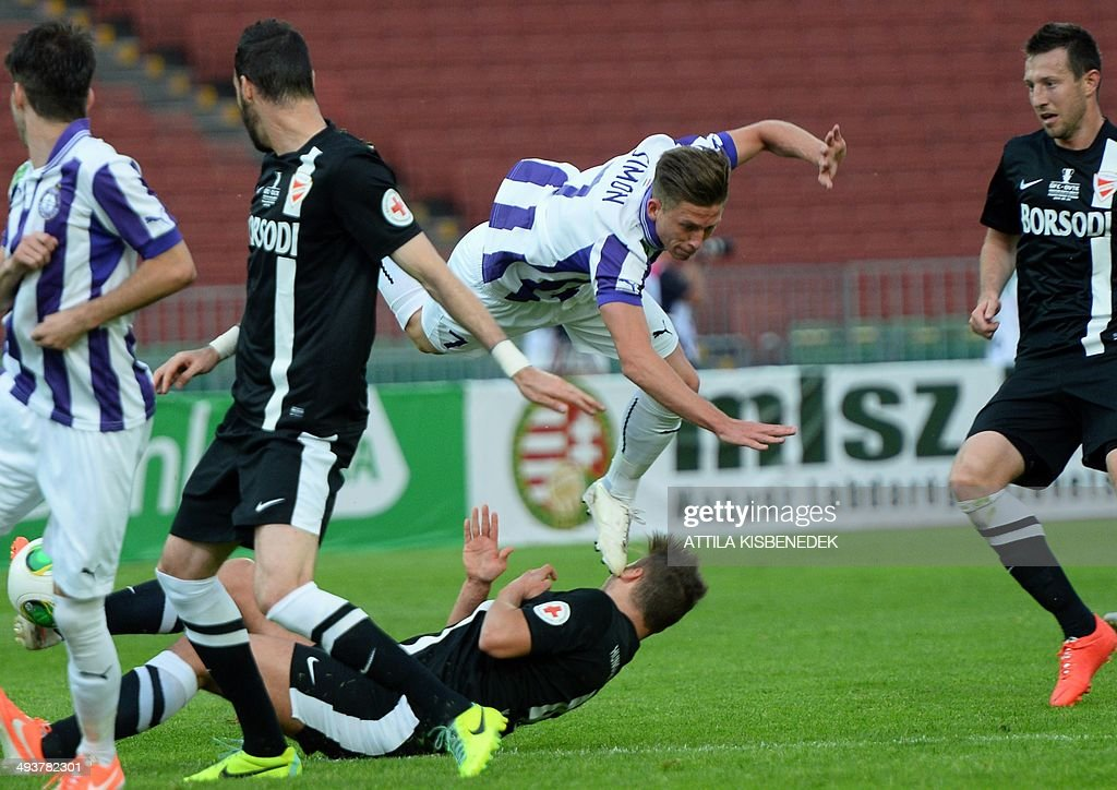Krisztian Simon (C) of TE Ujpest flies through the air between defenders of VTK Disosgyor during the Hungarian Cup final football match VTK Disosgyor vs TE Ujpest on May 25, 2014 at the Puskas stadium in Budapest.