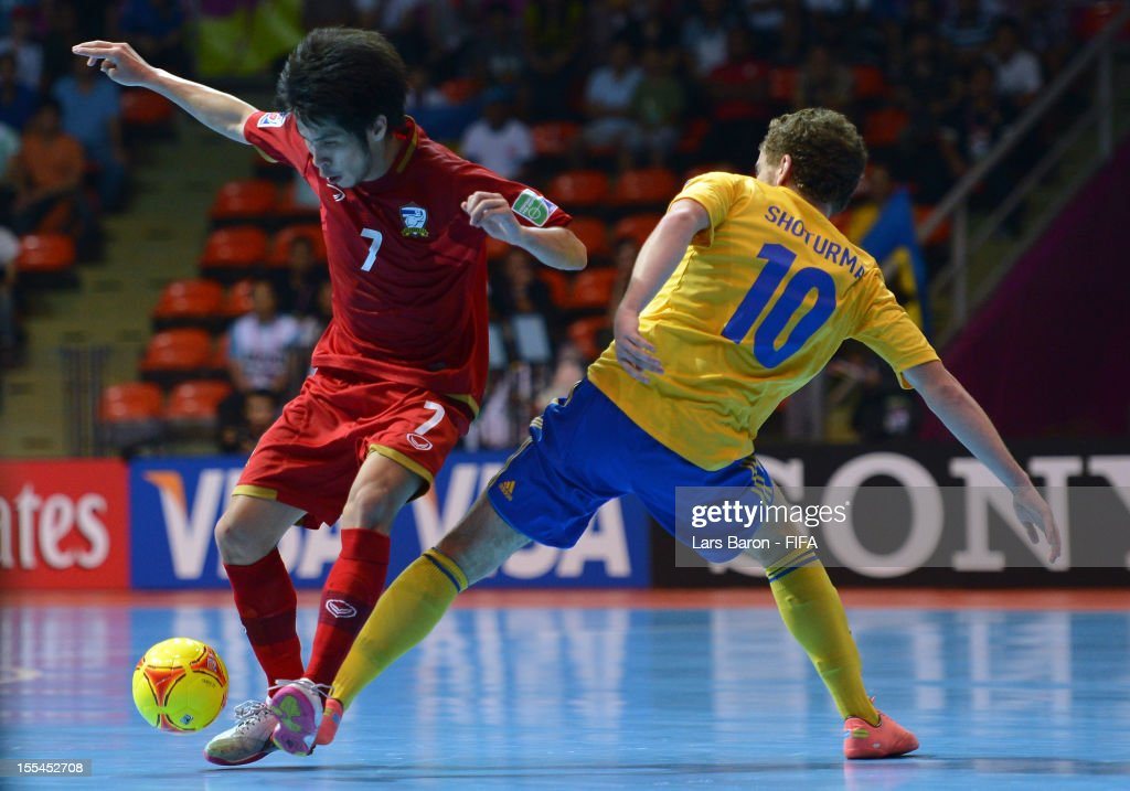 Kritsada Wongkaeo of Thailand is challenged by Petro Shoturma of Ukraine during the FIFA Futsal World Cup Group A match between Thailand and Ukraine at Indoor Stadium Huamark on November 4, 2012 in Bangkok, Thailand.