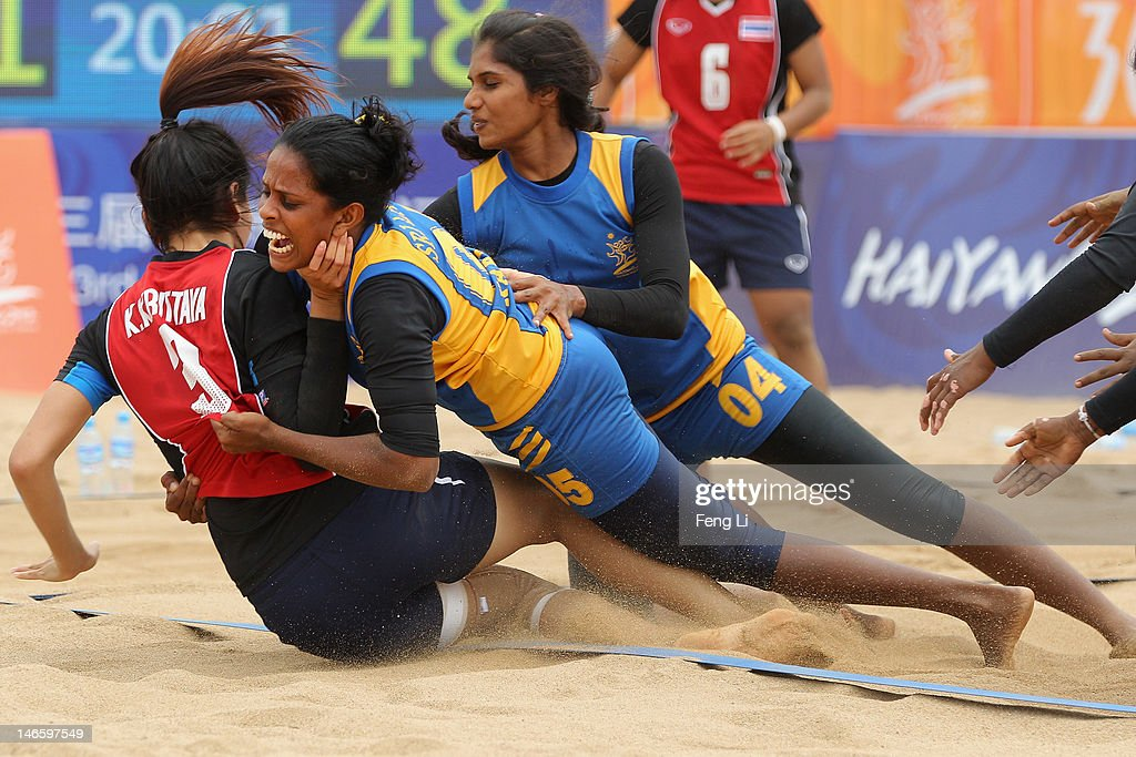 Krittaya Kwangkunthot (L) of Thailand is held by Dilini Wirapperuma Achchi Athuko of Sri Lanka during the Beach Kabaddi Women's Team Group A match between Thailand and Sri Lanka on Day 4 of the 3rd Asian Beach Games Haiyang 2012 at Fengxiang Beach on June 20, 2012 in Haiyang, China.