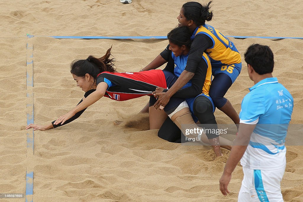 Krittaya Kwangkunthot (L) of Thailand reaches for the tape during the Beach Kabaddi Women's Team Group A match between Thailand and Sri Lanka on Day 4 of the 3rd Asian Beach Games Haiyang 2012 at Fengxiang Beach on June 20, 2012 in Haiyang, China.