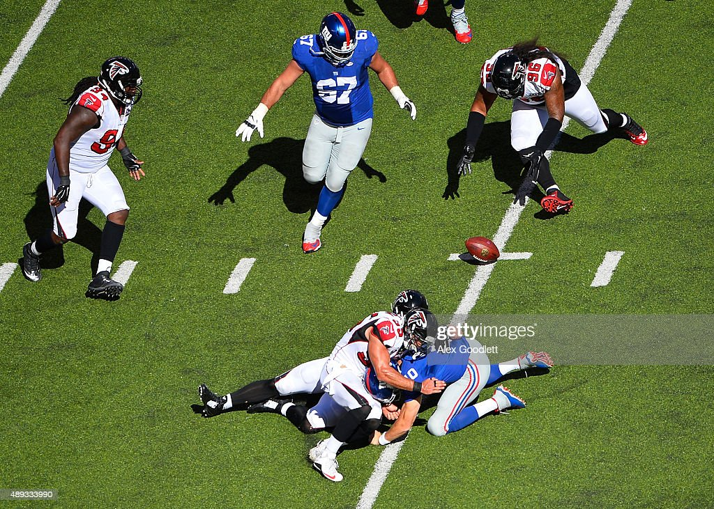 Kroy Biermann of the Atlanta Falcons forces a fumble in the third quarter from Eli Manning of the New York Giants and the ball is recovered by Paul...