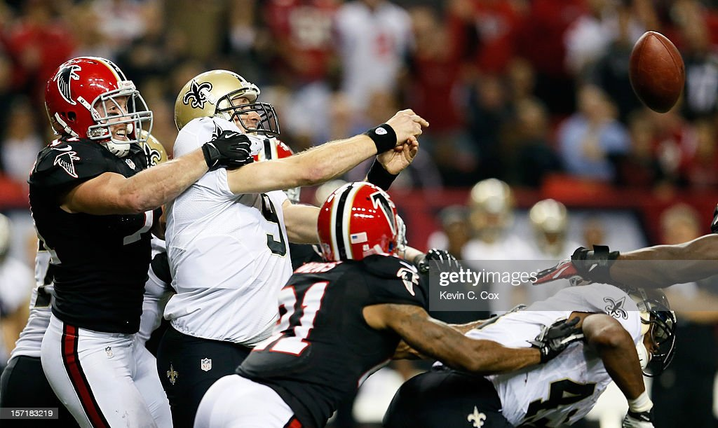 Kroy Biermann #71 of the Atlanta Falcons forces a interception by Drew Brees #9 of the New Orleans Saints at Georgia Dome on November 29, 2012 in Atlanta, Georgia.