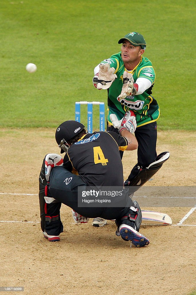 Kruger van Wyk of Central Districts fields the ball as Luke Ronchi of Wellington ducks for cover during the Twenty20 match between Wellington Firebirds and Central Stags at Hawkins Basin Reserve on December 26, 2012 in Wellington, New Zealand.