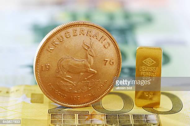 KrugerrandMünze und Goldbarren auf EuroScheinen Goldpreis