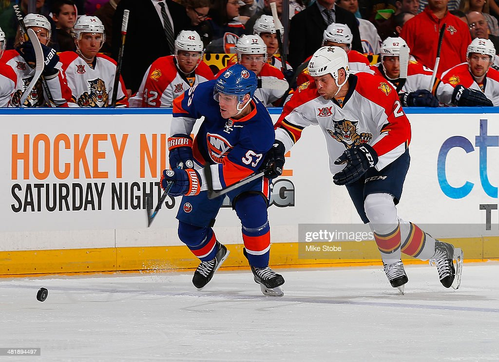 Krys Barch of the Florida Panthers and Casey Cizikas of the New York Islanders pursue a loose puck at Nassau Veterans Memorial Coliseum on April 1...