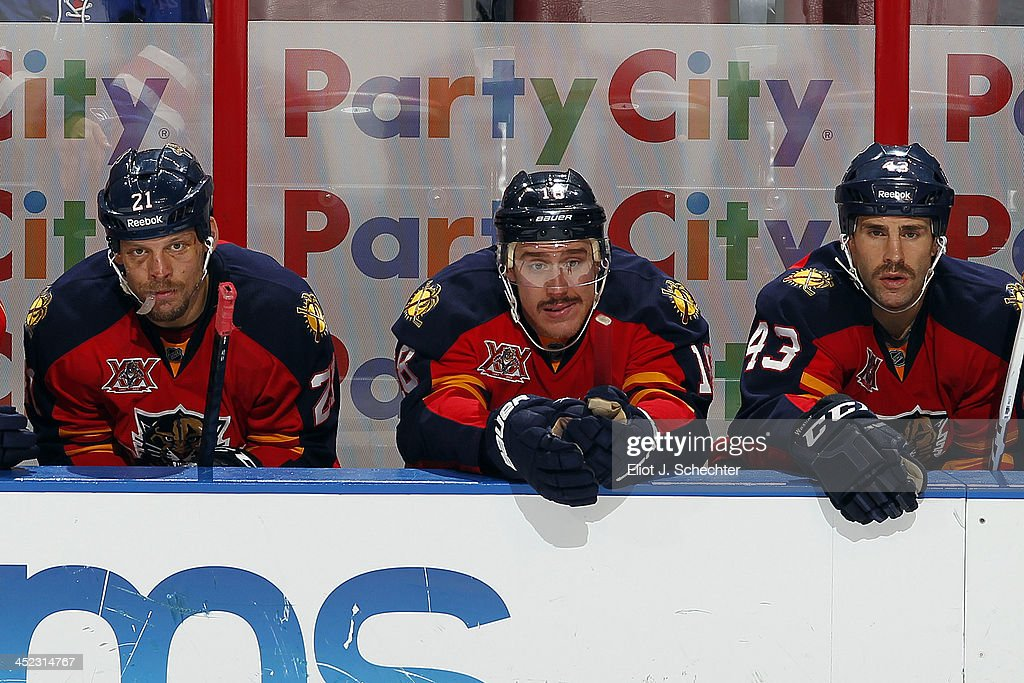 Krys Barch #21 of the Florida Panthers and teammates Shawn Matthias #18 and Mike Weaver #43 watch the action from the bench against the New York Rangers at the BB&T Center on November 27, 2013 in Sunrise, Florida.