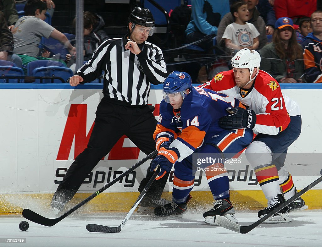Krys Barch of the Florida Panthers checks Thomas Hickey of the New York Islanders during the first period at the Nassau Veterans Memorial Coliseum on...