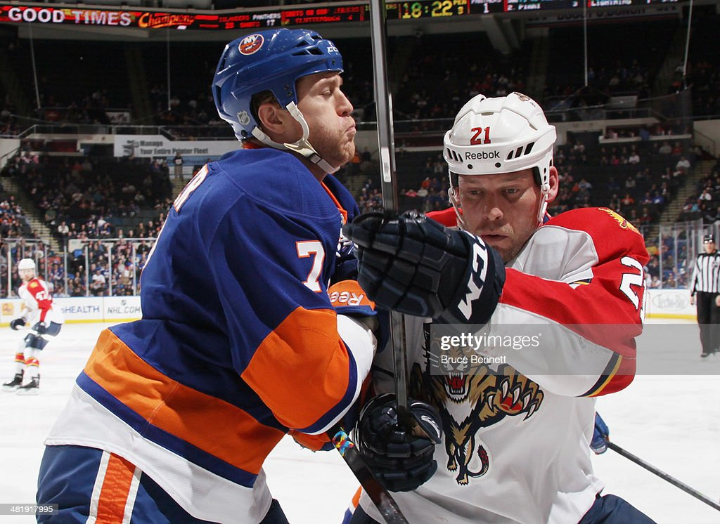 <a gi-track='captionPersonalityLinkClicked' href=/galleries/search?phrase=Krys+Barch&family=editorial&specificpeople=2538220 ng-click='$event.stopPropagation()'>Krys Barch</a> #21 of the Florida Panthers is hit by <a gi-track='captionPersonalityLinkClicked' href=/galleries/search?phrase=Matt+Carkner&family=editorial&specificpeople=556901 ng-click='$event.stopPropagation()'>Matt Carkner</a> #7 of the New York Islanders during the third period at the Nassau Veterans Memorial Coliseum on April 1, 2014 in Uniondale, New York. The Islanders defeated the Panthers 4-2.
