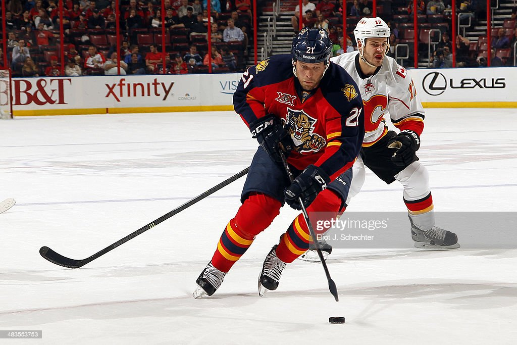 Krys Barch of the Florida Panthers skates with the puck against Lance Bouma of the Calgary Flames at the BBT Center on April 4 2014 in Sunrise Florida