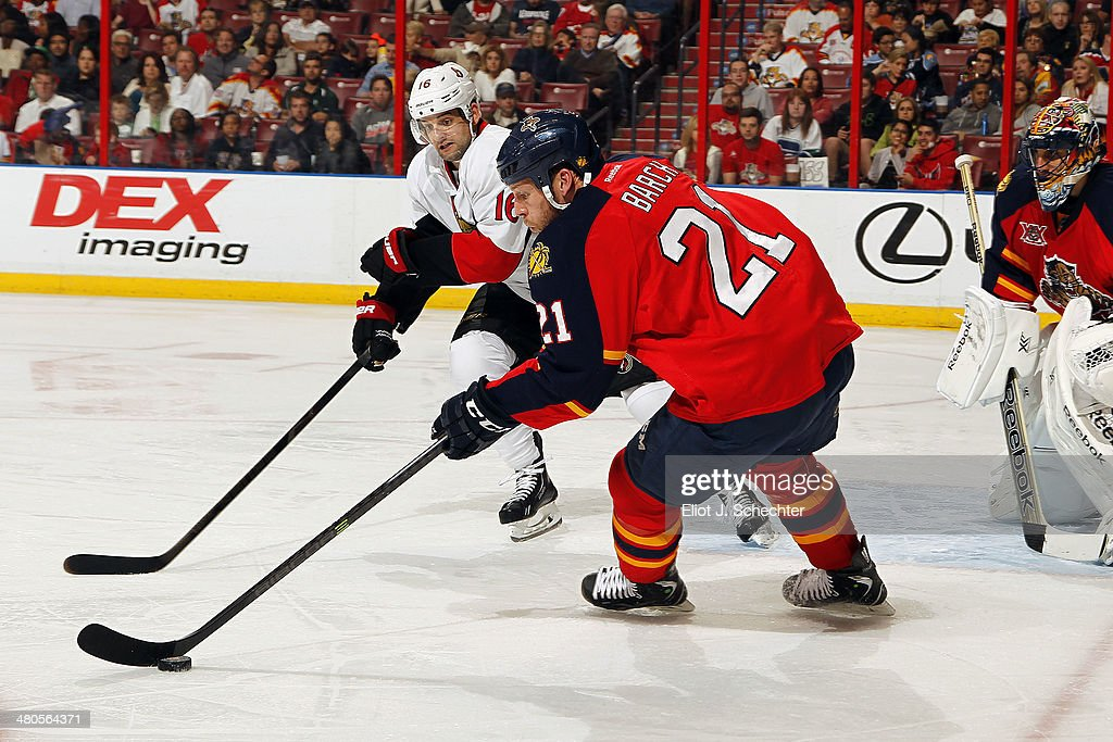 Krys Barch of the Florida Panthers skates with the puck against Clarke MacArthur of the Ottawa Senators at the BBT Center on March 25 2014 in Sunrise...