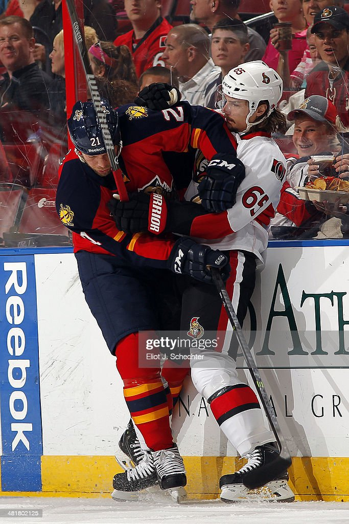 Krys Barch of the Florida Panthers tangles with Erik Karlsson of the Ottawa Senators at the BBT Center on March 25 2014 in Sunrise Florida