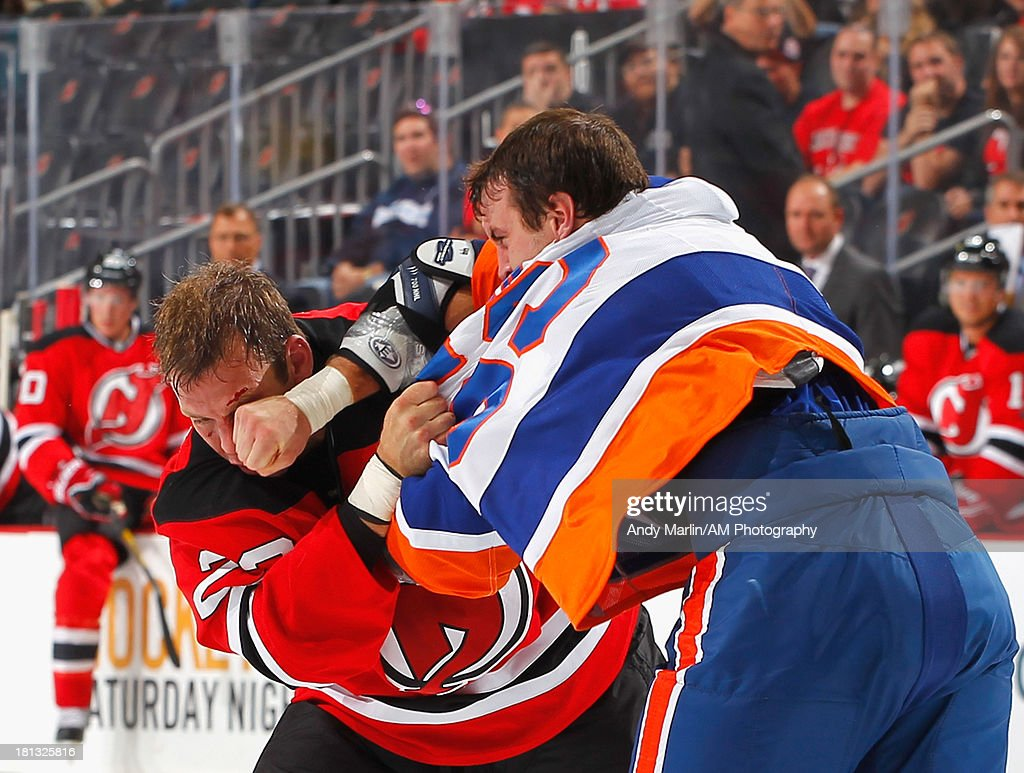 Krys Barch of the New Jersey Devils and Brett Gallant the New York Islanders fight during the preseason game at Prudential Center on September 19...