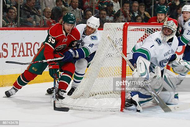 Krys Kolanos of the Minnesota Wild attempts a wraparound against Ryan Johnson of the Vancouver Canucks during the game at the Xcel Energy Center on...