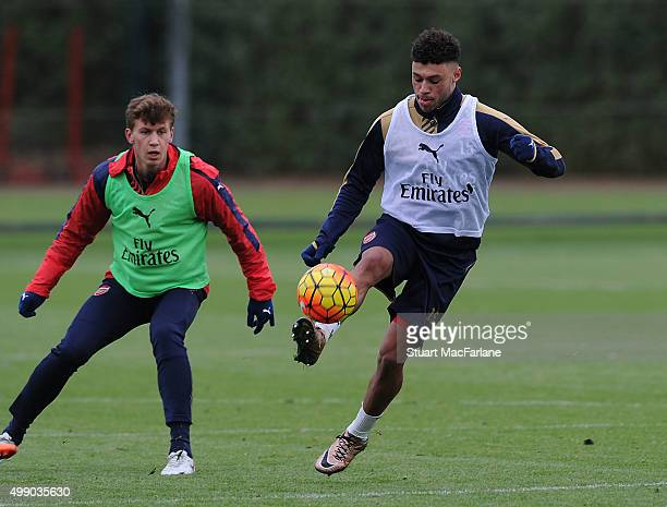 Krystain Bielik and Alex OxladeChamberlain of Arsenal during a training session at London Colney on November 28 2015 in St Albans England