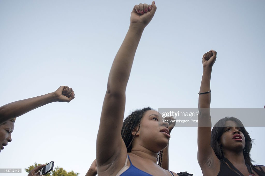 Krystal Leaphart (center) and Nasira Spells (right) sing the negro anthem Lift Every Voice and Sing along with hundreds that rally in support of shooting victim Trayvon Martin at Howard University in Washington, D.C. on July 14, 2013. Martin supporters react the day after George Zimmerman is acquitted.