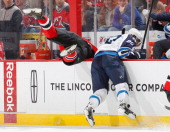 Krystofer Barch of the New Jersey Devils is checked into and over the boards by Nik Antropov of the Winnipeg Jetsduring the game at the Prudential...