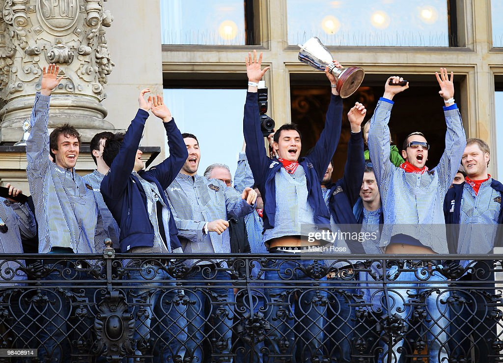 Krysztof Lijewski of Hamburg celebrates with his team mates with the cup at the Hamburg townhall after winning the DHB German Cup final match between...