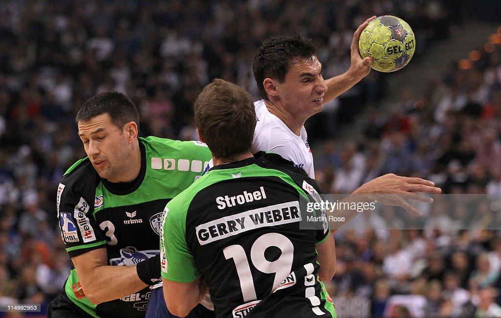 Kryzstof Lijewski of Hamburg is challenged by Ferenc Ilyes and Martin Strobel of Lemogo during the Toyota Handball Bundesliga match between HSV...