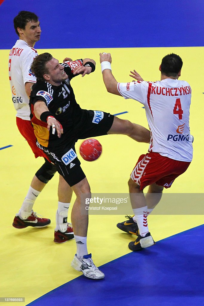 Krzysztof Lijewski (L) and Patryk Kuchczynski (R) of Poland defend against Lars Kaufmann of Germany (C) during the Men's European Handball Championship second round group one match between Poland and Germany at Beogradska Arena on January 25, 2012 in Belgrade, Serbia.
