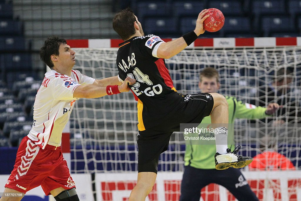 Krzysztof Lijewski of Poland defends against Michael Haass of Germany during the Men's European Handball Championship second round group one match between Poland and Germany at Beogradska Arena on January 25, 2012 in Belgrade, Serbia.