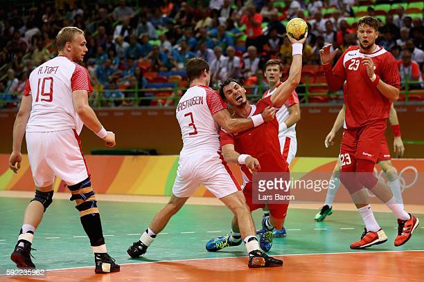 Krzysztof Lijewski of Poland gets blocked by Mads Christiansen of Denmark during the Men's Handball Semifinal match between Poland and Denmark on Day...