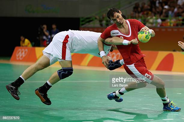 Krzysztof Lijewski of Poland is chased by Henrik Hansen of Denmark during the Men's Handball Semifinal match between Poland and Denmark on Day 14 of...