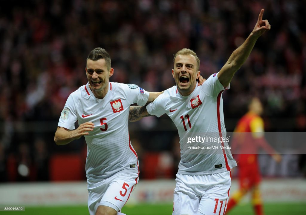 Krzysztof Maczynski of Poland (L) celebrates with team-mate Kamil Grosicki after scoring the opening goal during the FIFA 2018 World Cup Qualifier between Poland and Montenegro on October 8, 2017 in Warsaw, Poland.