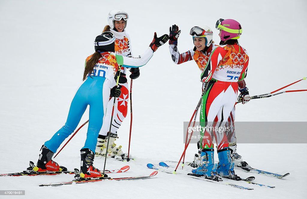 Kseniya Grigoreva of Uzbekistan (L) and Suela Mehilli of Albania (2R) greet each other as Elise Pellegrin of Malta (2L) and Camille Dias of Portugal look on during the Alpine Skiing Women's Giant Slalom on day 11 of the Sochi 2014 Winter Olympics at Rosa Khutor Alpine Center on February 18, 2014 in Sochi, Russia.