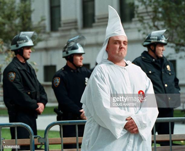 A Ku Klux Klan member stands with heavy police protection during a rally in New York 23 October 1999 A crowd of several hundred antiKlan protesters...