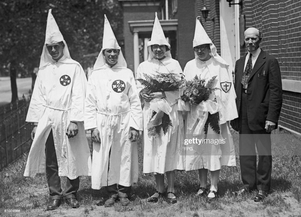 A Ku Klux Klan wedding in Washington DC, during the mass Klan demonstration, 1925. From left to right, Carson Sanders (the best man), Mr and Mrs Charles E. Harris (the bride and groom), Miss Dorothy Lucas (sister of the bride) and Reverend Carroll Maddox of the First MP Church of Washington.