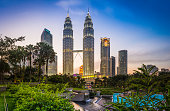 The iconic twin spires of the Petronas Towers glittering against the blue dusk sky above the ponds of KLCC Park and Suria KLCC in the heart of Kuala Lumpur, Malaysia's vibrant capital city. ProPhoto R