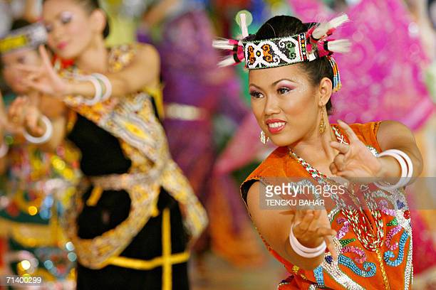 A dancer wearing a traditional tribal costume from Malaysian Borneo performs during the Citrawarna festival parade in downtown Kuala Lumpur late 08...