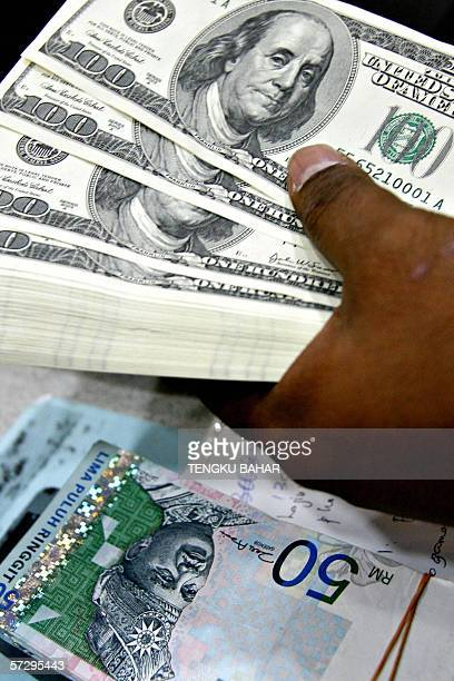 A money changer holds a wad of USD bills next to a stack of RM50 Malaysian ringgit bills at a currency exchange in Kuala Lumpur 07 April 2006 The...
