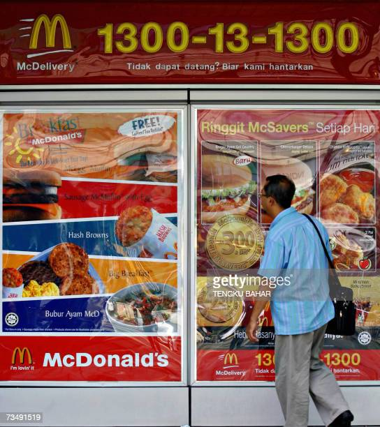 A pedestrian walks past a billboard listing menu items in front of a McDonald's fast food chain restaurant in downtown Kuala Lumpur 05 March 2007...