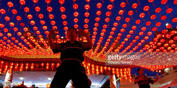 A Tai Chi martial arts practitioner performs exercises underneath lanterns at twilight on the premises of a Chinese temple in Kuala Lumpur 16...