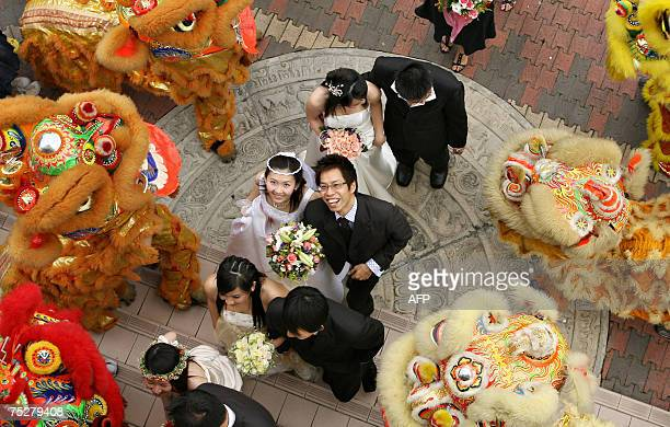 Couples walk past a troupe of lion dancers as they enter a ceremonial hall for a mass wedding at a Buddhist temple in Kuala Lumpur 07 July 2007 Fifty...