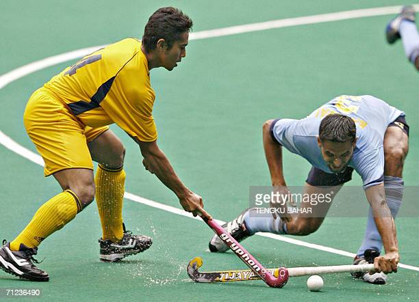 India's Sandeep Singh attempts to intercept the ball from Malaysia's Azlan Misron's control during the second day of the Sultan Azlan Shah hockey...