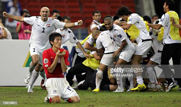 Iraqi football players celebrate their victory as South Korea's Kim Jungwoo looks on during the Asian Football Cup semifinal match between Iraq and...