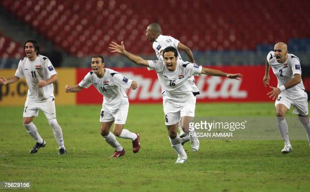Iraqi players celebrate after their goalkeeper Noor Sabri Abbas makes a save to put South Korea ahead during a penalty shootout at the Asian Football...