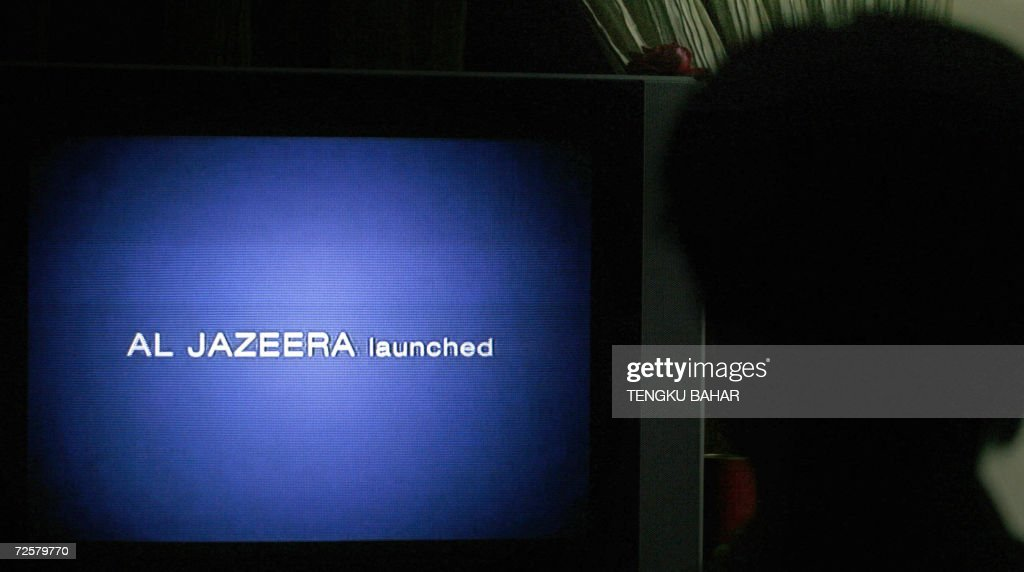 Tarmizi Ibrahim is sihouetted against a television screen as he watches the launching of the Al-Jazeera English news service, launched at 1200 GMT, in Kuala Lumpur, 15 November 2006. Al-Jazeera, the Middle East news channel launched its English-language channel 15 November in Asia and vowed to provide a different news perspective at a time when this booming economic region is hungry for news.